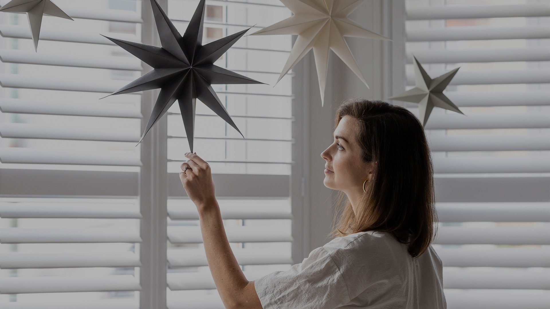 A woman touches a paper star hanging from her ceiling, in front of shuttered windows.